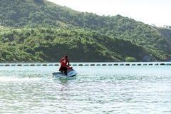 Uomo su Jet Ski divertendosi nell'oceano Immagini Stock