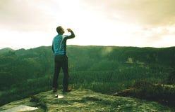 Uomo su un bordo della scogliera sopra la montagna con la vista splendida fotografie stock libere da diritti