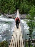 Uomo su un ponte sospeso fotografia stock
