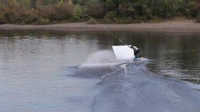 Uomo su un wakeboard che fa una vibrazione posteriore da un trampolino Bella ed acrobazia pericolosa wakepark archivi video