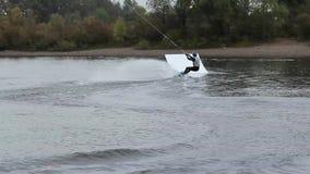 Uomo su un wakeboard che fa una vibrazione posteriore da un trampolino Bella ed acrobazia pericolosa wakepark video d archivio