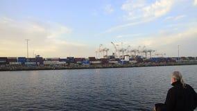 Uomo su una barca che esamina i cotainers del carico il porto di Long Beach, California stock footage
