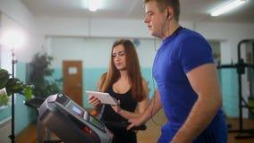 Uomo su una pedana mobile nella ragazza della palestra sull'istruttore della pedana mobile, sport uno stile di vita sano archivi video