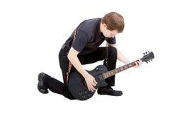 Uomo su una priorità bassa bianca Esecutore con una chitarra elettrica Immagini Stock