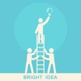 Uomo su una scala che tiene una lampadina Concetto di lavoro di squadra e di sostegno Fotografia Stock