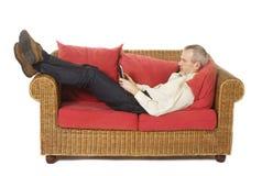 Uomo su uno strato con un e-lettore. Immagine Stock Libera da Diritti