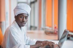 Uomo sudanese di affari in attrezzatura tradizionale facendo uso del telefono cellulare in ufficio Immagine Stock
