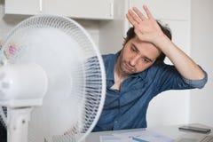 Uomo sudato che prova a rinfrescare da calore con il fan immagini stock libere da diritti