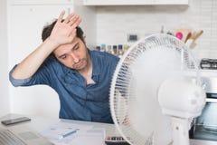 Uomo sudato che prova a rinfrescare da calore con un fan immagine stock