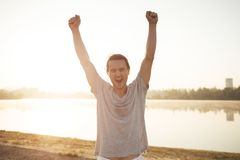 Uomo sudato con le mani sollevate felici di finire allenamento su alba Immagine Stock