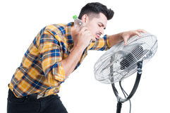 Uomo sudato ed assetato che sta fan vicino e raffreddarsi Immagini Stock