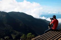 Uomo sul bordo della scogliera che fotografa natura Fotografie Stock
