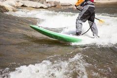 Uomo sul bordo di pagaia in piedi su un fiume veloce Immagini Stock