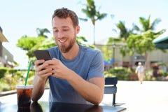 Uomo sul caffè facendo uso di invio di messaggi di testo di app dello Smart Phone Fotografia Stock