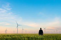 Uomo sul campo di grano verde con i mulini a vento per produzione di energia elettrica Fotografia Stock