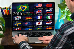 Uomo sul computer che guarda un canale di sport olimpici sul onlin della TV Fotografia Stock