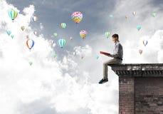 Uomo sul libro di lettura del bordo del tetto ed aerostati che volano in cielo Immagini Stock