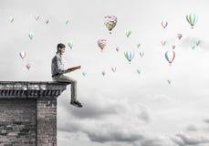 Uomo sul libro di lettura del bordo del tetto ed aerostati che volano in cielo Immagine Stock