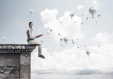 Uomo sul libro di lettura del bordo del tetto ed aerostati che volano in cielo Fotografia Stock Libera da Diritti