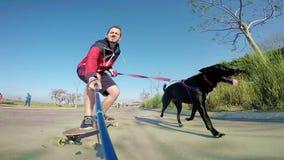 Uomo sul longboard con il cane stock footage