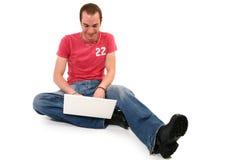 Uomo sul pavimento con il computer portatile Immagini Stock Libere da Diritti
