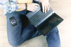 Uomo sul pavimento con un computer portatile fotografie stock