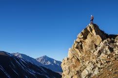 Uomo sul picco che esamina le montagne Immagine Stock Libera da Diritti