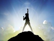 Uomo sul picco della montagna e del suntlight, successo, vincitore concentrato Immagine Stock