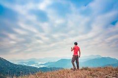Uomo sul picco Facendo un'escursione in autunno Fotografia Stock