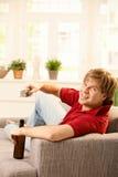 Uomo sul sofà con telecomando Fotografia Stock Libera da Diritti