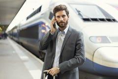 Uomo sul telefono cellulare Stazione della piattaforma Treno su fondo fotografie stock