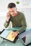 Uomo sul telefono che controlla le sue note fotografia stock libera da diritti