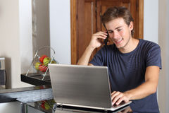 Uomo sul telefono che funziona con un computer portatile a casa Immagini Stock