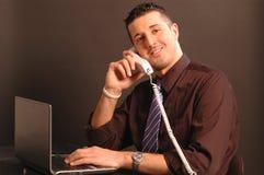 Uomo sul telefono mentre sul calcolatore 2431 Fotografia Stock