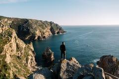 Uomo sull'orlo della pietra sulla riva dell'oceano, Portogallo Immagini Stock Libere da Diritti