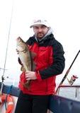 Uomo sulla barca con i pesci di merluzzo Immagine Stock