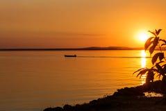 Uomo sulla barca durante il tramonto sul lago Fotografie Stock