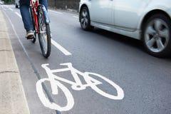 Uomo sulla bici facendo uso del vicolo del ciclo come velocità di traffico oltre Immagine Stock