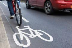 Uomo sulla bici facendo uso del vicolo del ciclo come velocità di traffico oltre Fotografia Stock