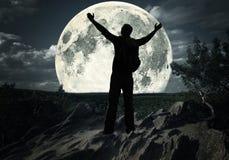 Uomo sulla cima della montagna che esamina la luna Fotografia Stock Libera da Diritti
