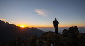 Uomo sulla cima di una roccia Fotografia Stock