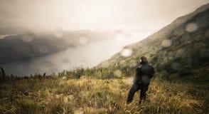 Uomo sulla collina che esamina il fiume immagine stock