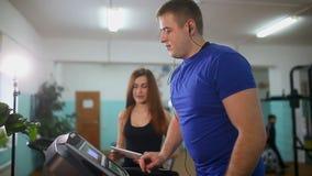 Uomo sulla pedana mobile nella ragazza della palestra sull'istruttore della pedana mobile, sport uno stile di vita sano video d archivio