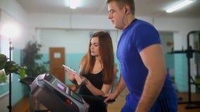 Uomo sulla pedana mobile nella ragazza della palestra sull'istruttore della pedana mobile, sport uno stile di vita sano archivi video