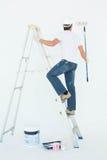 Uomo sulla pittura della scala con il rullo Fotografie Stock Libere da Diritti