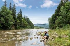 Uomo sulla riva di un fiume della montagna Immagine Stock Libera da Diritti