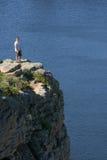 Uomo sulla scogliera vicino al lago Fotografia Stock Libera da Diritti