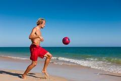 Uomo sulla sfera di calcio d'equilibratura della spiaggia Fotografia Stock Libera da Diritti