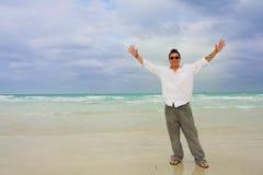 Uomo sulla spiaggia con le braccia estese Fotografia Stock Libera da Diritti