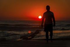 Uomo sulla spiaggia durante l'alba Fotografia Stock